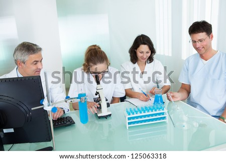 Paramedical or technical staff grouped together looking at a computer in a laboratory - stock photo