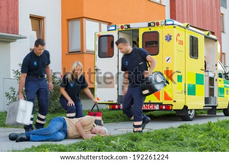 Paramedical team arriving to unconscious elderly man lying on street - stock photo