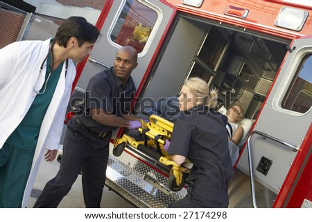 Paramedics and doctor unloading patient from ambulance - stock photo