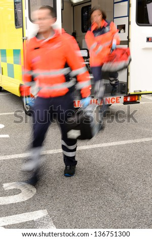 Paramedics jumping out from ambulance car in emergency situation - stock photo