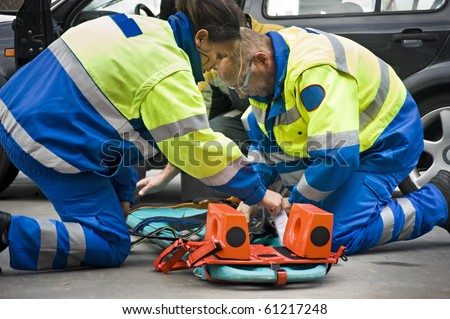 Paramedics preparing a stretcher for a wounded car accident victim - stock photo