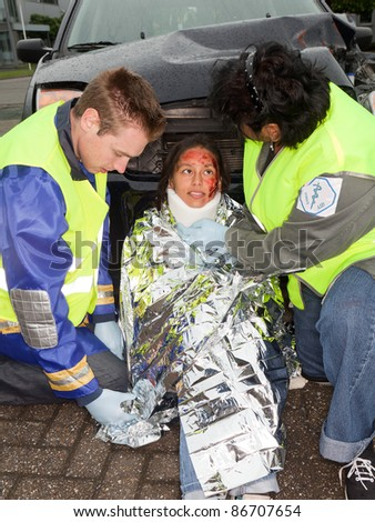 Paramedics putting a protective blanket on a car crash victim (the sleeve badges have been replaced by a non existing logo) - stock photo