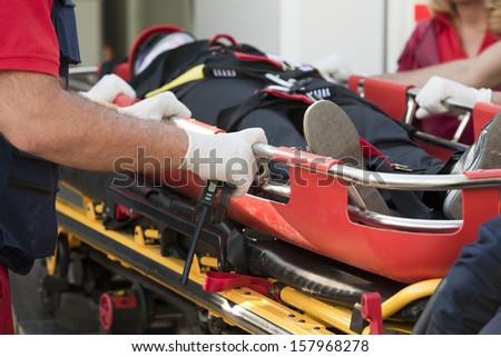 Paramedics rushing patient into an ambulance - stock photo