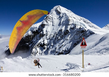 Paramotor and Snow Mountain in Switzerland. - stock photo