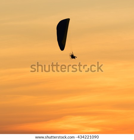 Paramotor flying on the sky in big sun at sunset