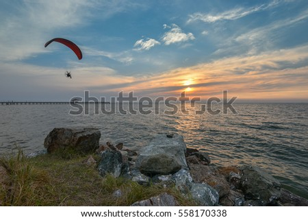 Paramotor over the sea at sunset time