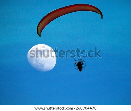 paramotor silhouette with the moon - stock photo