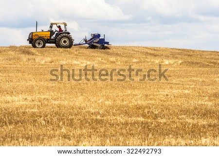 Parana, Brazil, December 08, 2009: Farmer in tractor sowing crops at field with seed scattering agricultural machine