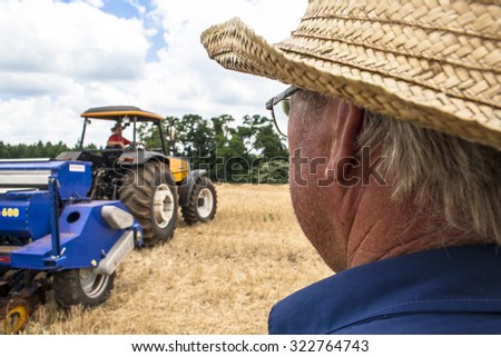 Parana, Brazil, December 08, 2009: Farmer in tractor sowing crops at field with seed scattering agricultural machine and another farmer checks planting in field.