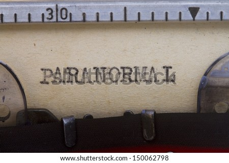Paranormal typewritten in a vintage paper close up shot.