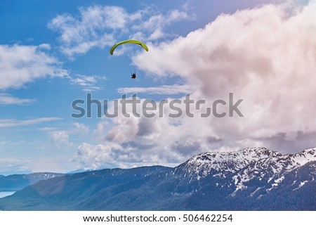 paraplane in blue sky with mountain skyline