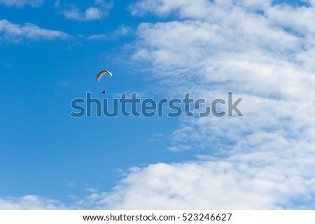 Paraplane in the blue sky with clouds