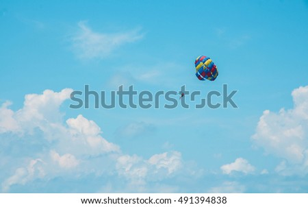 Parasailing against a blue sky and cloud. Lamai Beach, Samui, Thailand.Image has grain or blurry or noise and soft focus when view at full resolution.
