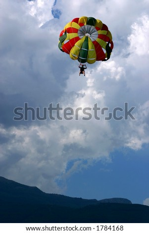 Parasailing against cloudy sky
