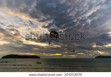Parasailing in silhouette with beauty cloudy formation cloud - stock photo