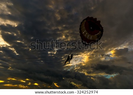 Parasailing in silhouette with cloudy formation cloud