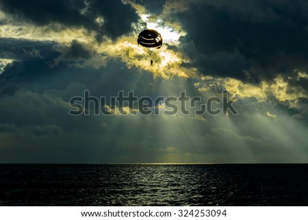 Parasailing in silhouette with cloudy formation cloud and ray of lights - stock photo