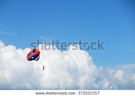 Parasailing man against cumulus clouds and a blue sky