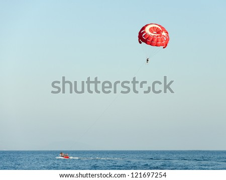 Parasailing on a red parachute over water - stock photo