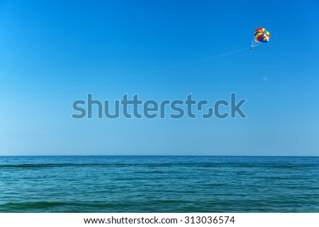parasailing over the sea, sea, sky, activity, blue, parachute, people, summer, water, travel, entertainment, outdoor, tropical air, wind, extreme - stock photo