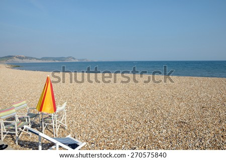 Parasol and table at Lyme Regis, Dorset - stock photo