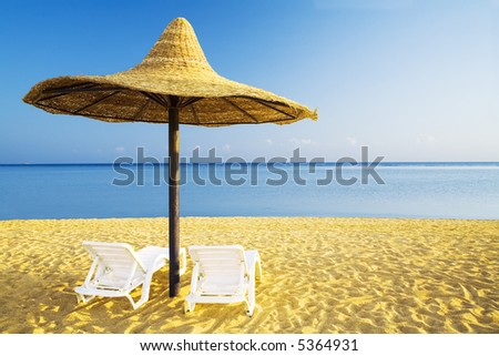 parasol and two deckchairs on the sand beach, (early morning) - stock photo