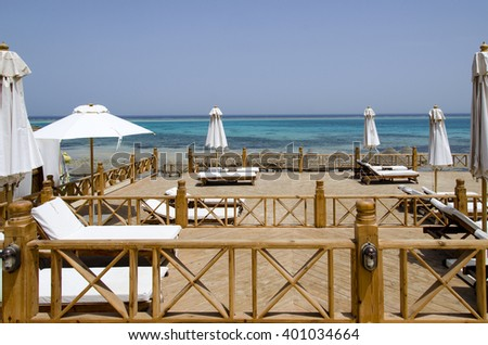 Parasols and sun chairs on the Sand near Sea - stock photo