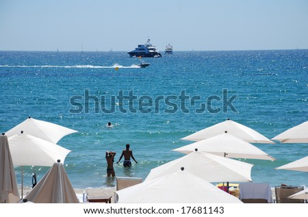 Parasols on the beach in Cannes - stock photo