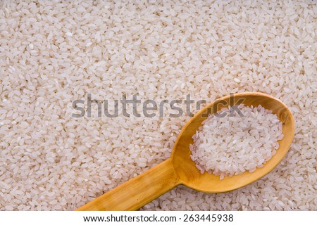 Parboiled rice grains with a rustic wooden kitchen spoon in an overhead background food texture - stock photo