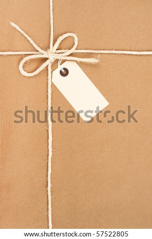 Parcel tied with string with address label attached - stock photo