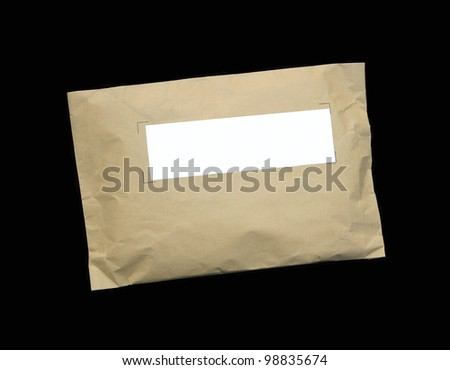 Parcel wrapped in brown paper with blank label for your text isolated on black background. - stock photo