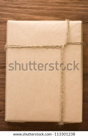 parcel wrapped packaged box on wood background - stock photo