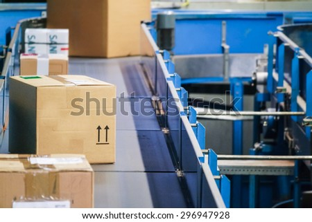 Parcels on conveyors with blurred industrial background - stock photo