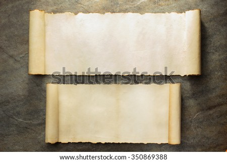 parchment scroll on stone wall background - stock photo