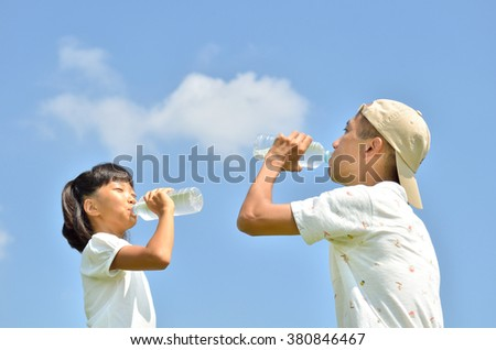 Parent and children to drink water in the blue sky
