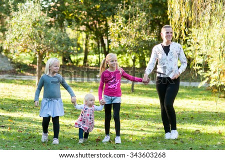 Parent and their children are walking in the park with holding hands on a sunny day in the park. - stock photo
