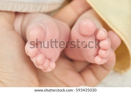 Parent holding in the hand feet of newborn baby