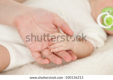 parent's hand holding baby's hand
