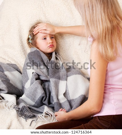 Parent touching forehead child. Illness child