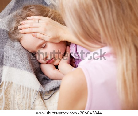 Parent touching forehead child. Illness child - stock photo