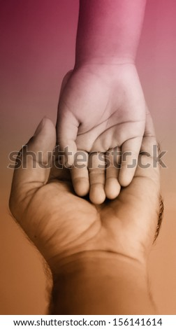 parental hand holds hand the baby  - stock photo