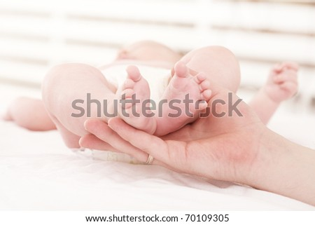 parental hand holds legs of the baby
