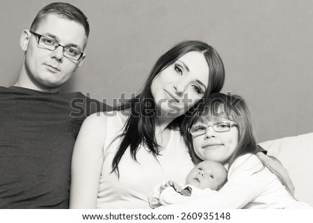 Parenthood and happiness concept. Young family mother father and child preschooler sitting on sofa with newborn baby girl at home. Black & white - stock photo