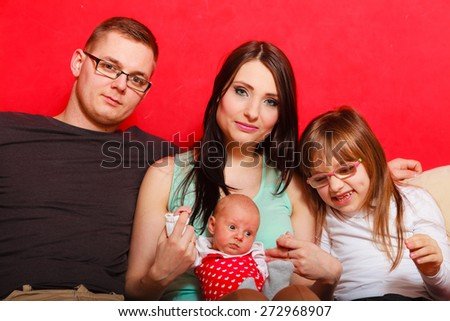 Parenthood and happiness concept. Young family mother father and child preschooler sitting on sofa with newborn baby girl at home