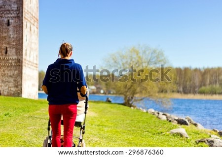 Parenthood concept image: happy mother walking with baby stroller on the lake shore. View from back