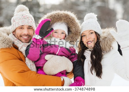 parenthood, fashion, gesture, season and people concept - happy family with child in winter clothes waving hands outdoors - stock photo