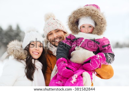 parenthood, fashion, season and people concept - happy family with child in winter clothes outdoors - stock photo