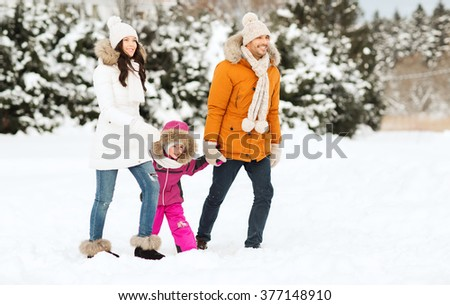 parenthood, fashion, season and people concept - happy family with child in winter clothes walking outdoors - stock photo