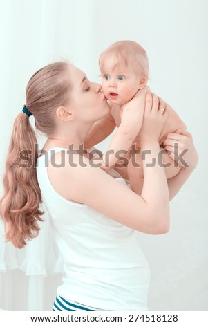 Parenthood. Young mother holding and kissing her surprised baby  - stock photo