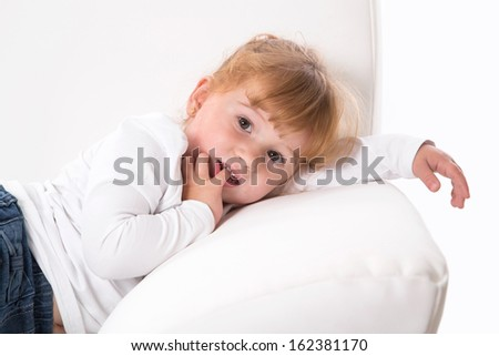 Parenting - cute shy girl sucking thumb - lying at sofa - fever